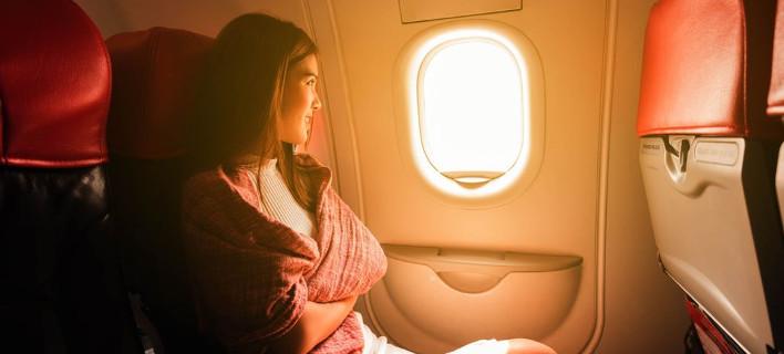 Γυναίκα κοιτάζει έξω από το παράθυρο αεροπλάνου/Φωτογραφία Shutterstock