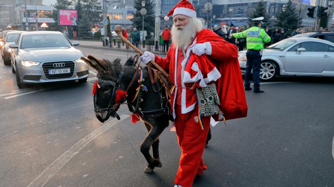 Ενας ταπεινός Αϊ-Βασίλης με το γαϊδουράκι του, στη Ρουμανία -Φωτογραφία: AP Photo/Vadim Ghirda