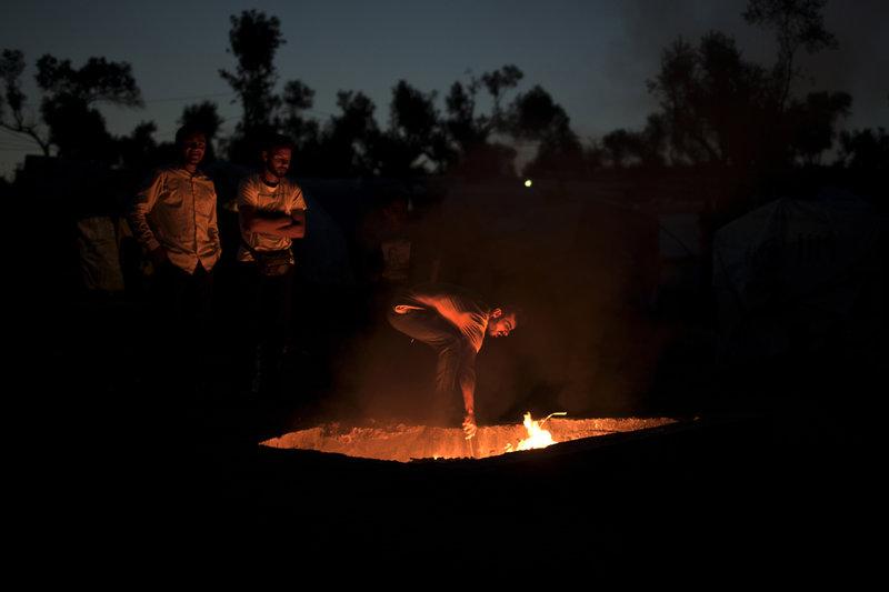 Πρόσφυγες καίνε σκουπίδια σε λάκο για να ζεσταθούν στον καταυλισμό της Μόρια (Φωτιογραφία: ΑΡ)