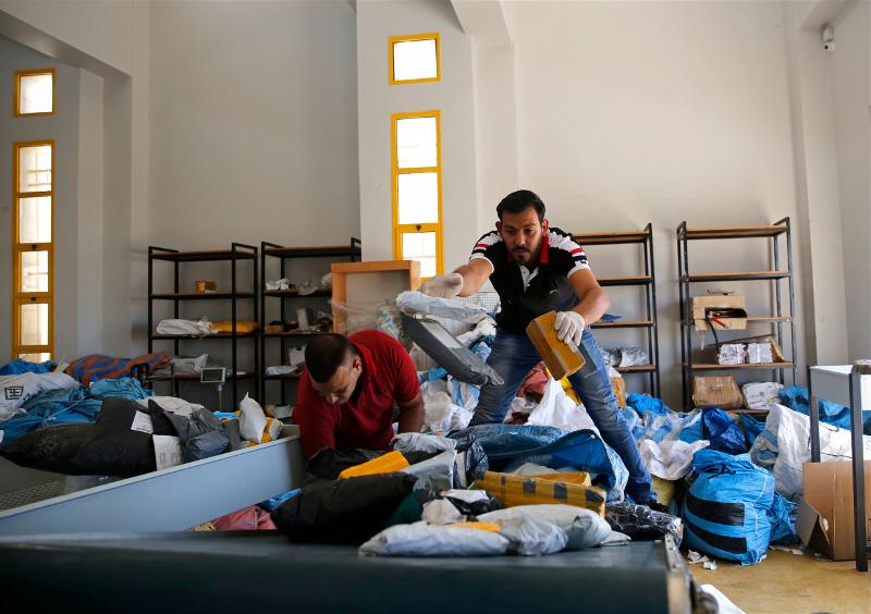 Παλαιστίνιοι υπάλληλοι εργάζονται πυρετωδώς για να ταξινομήσουν τα γράμματα του ταχυδρομείου/Φωτογραφία: AP/Nasser Shiyoukhi