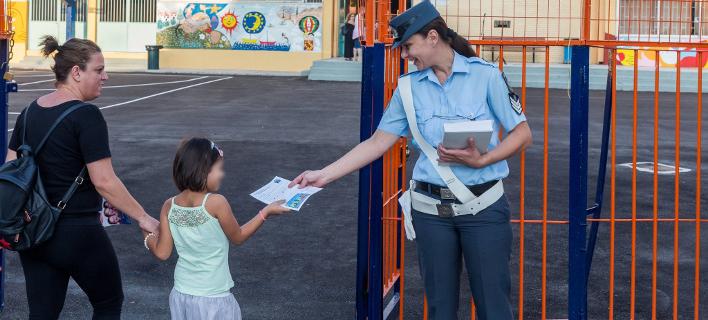 Αστυνομικός μοιράζει φυλλάδια σε μαθητές / Εικόνα αρχείου: EUROKINISSI