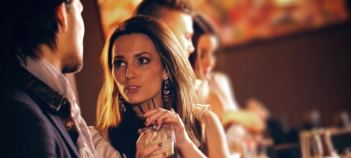 Μια γυναίκα πίνει το ποτό της σε ένα μπαρ, Φωτογραφία: Shutterstock/Jacob Lund