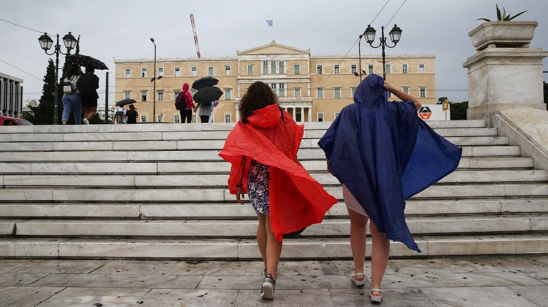 Εξω από τη Βουλή, ένα κόκκινο και ένα μπλέ αδιάβροχο. Οπως οι γραβάτες Τσίπρα-Καμμένου -Φωτογραφία: Intimenews/ΛΙΑΚΟΣ ΓΙΑΝΝΗΣ