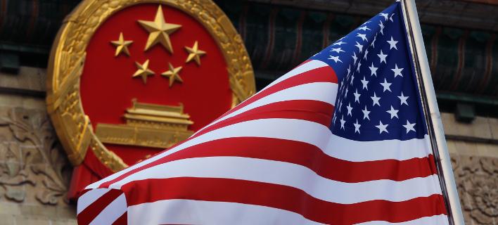 Αμερικανική σημαία μπροστά από το σύμβολο της Κίνας/Φωτογραφία: ΑΡ