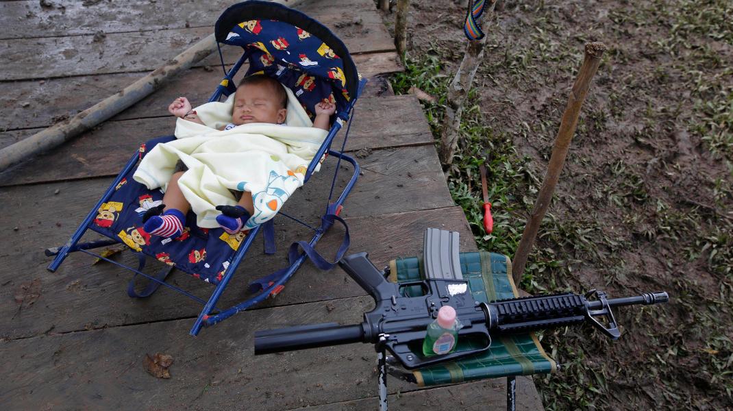 Μια άλλη εκδοχή της ημέρας της γυναίκας: Αντάρτισσα του FARC στην Κολομβία κοιμίζει το γιο της δίπλα στο όπλο της -Φωτογραφία: AP Photo/Fernando Vergara