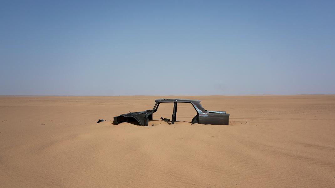 Ενα εγκαταλελειμμένο αυτοκίνητο στην έρημο Σαχάρα -Στο δρόμο που πια χρησιμοποιούν πρόσφυγες -Φωτογραφία: AP Photo/Jerome Delay