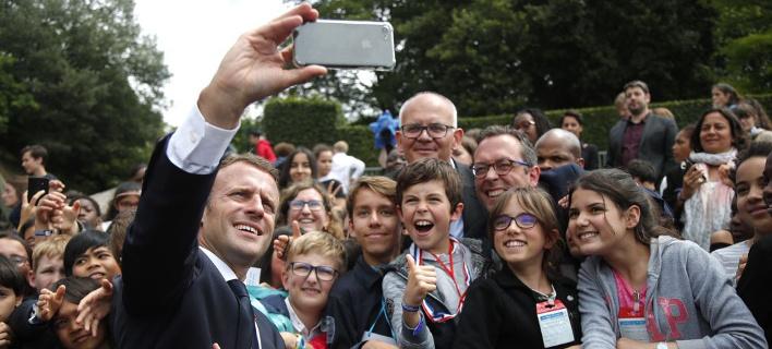 Ο Εμανουέλ Μακρόν με μαθητές. Φωτογραφία: AP Images