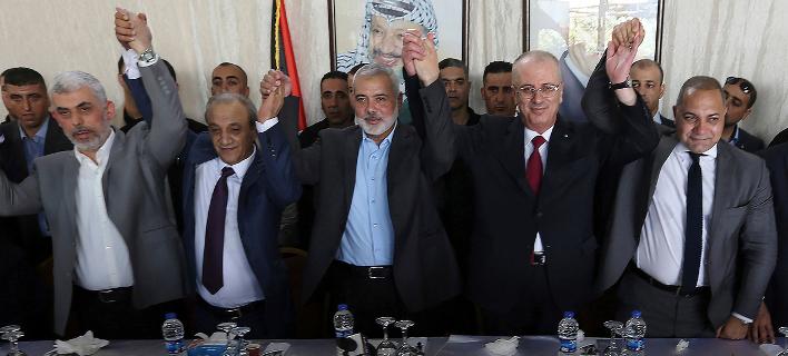 O Παλαιστίνιος πρωθυπουργός Ραμί Χαμντάλα κρατά το χέρι του ηγέτη της Χαμάς στη Γάζα, Ισμαήλ Χανίγιε (Φωτογραφία: ΑΡ)