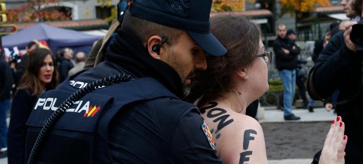Αστυνομικοί απομακρύνουν τις ακτιβίστριες των Femen (Φωτογραφία: ΑΡ/Manu Fernandez)