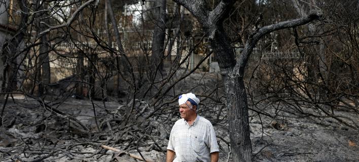 Eνας κάτοικος στο καμένο δάσος στο Μάτι-Φωτογραφία: AP/Τhanassis Stavrakis