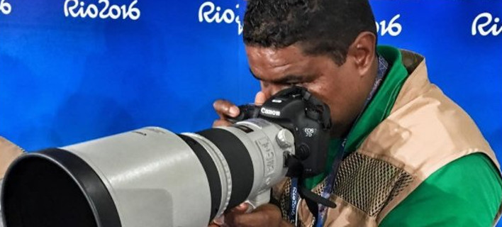 João Maia trabalhando no Rio2016 sentado de costas para um painel azul olhando no visor da câmera profissional com uma lente fixa de 300 mm da série branca da Canon . João usa camiseta verde e colete de imprensa marrom.
