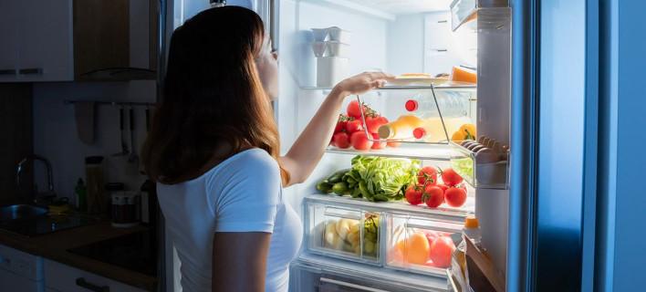 Μια γυναίκα ψάχνει στο ψυγείο να φάει, Φωτογραφία: Shutterstock