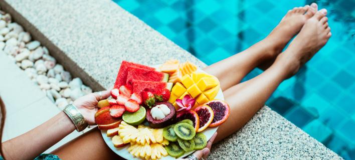 Μια γυναίκα τρώει φρούτα στην πισίνα, Φωτογραφία: Shutterstock/ By Alena Ozerova