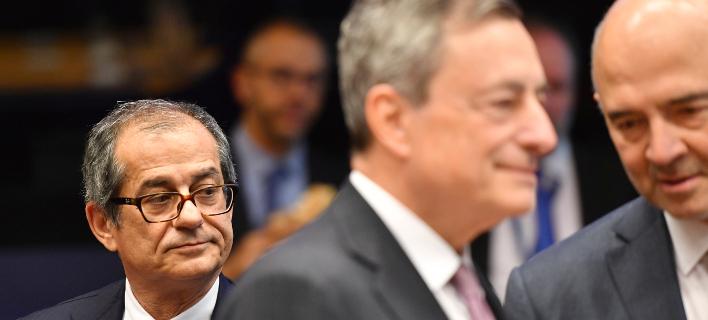 O Ιταλός υπουργός Οικονομικών Τζιοβάνι Τρία (αριστερά) με το βλέμμα στον Μάριο Ντράγκι και τον Πιερ Μοσκοβισί (Φωτογραφία: ΑΡ/Geert Vanden Wijngaert)