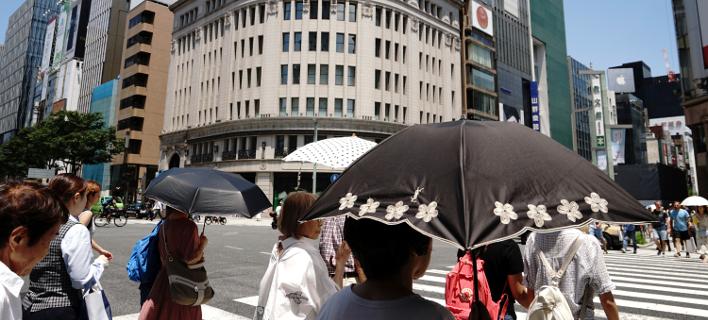 Mε ομπρέλες για προστασία από την ήλιο κυκλοφορούν οι κάτοικοι στο Τόκυο/Φωτογραφία: ΑΡ