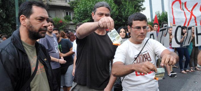 Μέλη του ΑΝΤΑΡΣΥΑ έκαψαν ευρώ έξω από τα γραφεία της ΕΕ και ...έφτυσαν τον Βαρουφάκη [εικόνες]