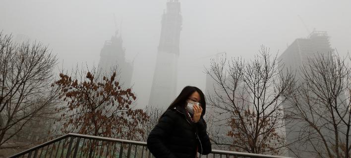 Γυναίκα προσπαθεί να προστατευθεί από την ατμοσφαιρική ρύπανση στο Πεκίνο / Φωτογραφία: ΑΡ