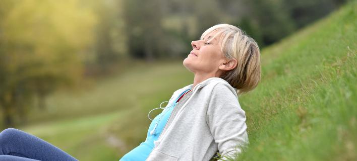 Μια γυναίκα χαλαρώνει στο γκαζόν, Φωτογραφία: Shutterstock/By goodluz
