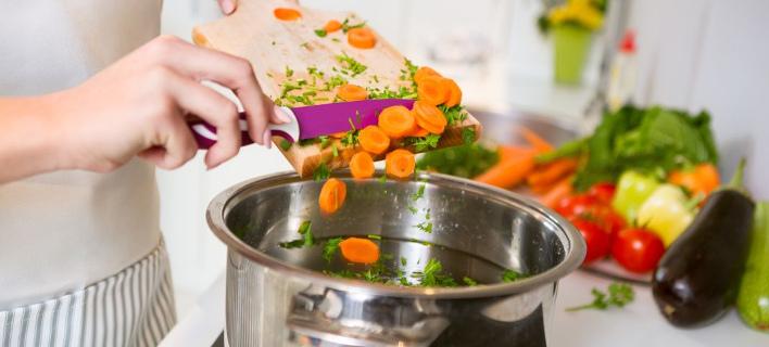 Μια γυναίκα μαγειρεύει στην κουζίνα του σπιτιού/ Φωτογραφία: Shutterstock