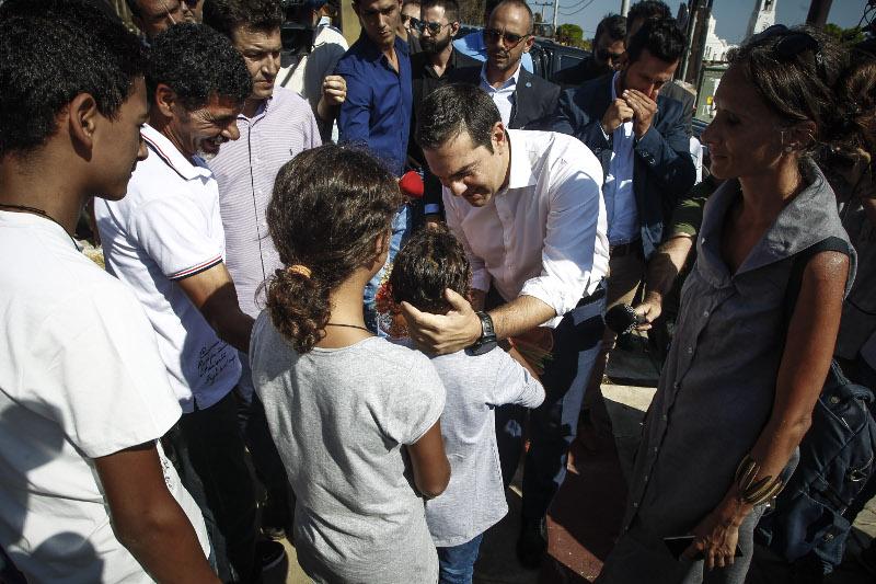 Ο Αλέξης Τσίπρας χαιδεύει το κεφάλι ενός παιδιού που τον υποδέχθηκε- φωτογραφία eurokinissi