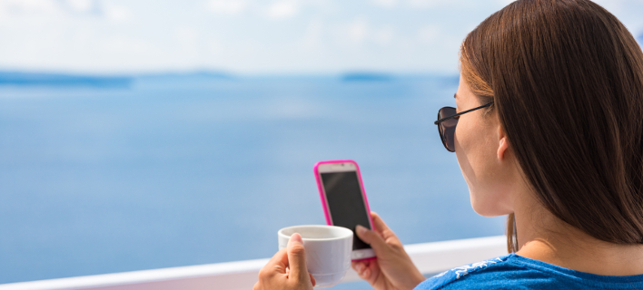 Μια γυναίκα πίνει τον καφέ της και κοιτάει το κινητό της, Φωτογραφία: Shutterstock/By Maridav