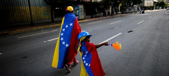 Διαδηλωτής μαζί με το παιδί του σε δρόμο του Καράκας. AP Photo/Ariana Cubillos