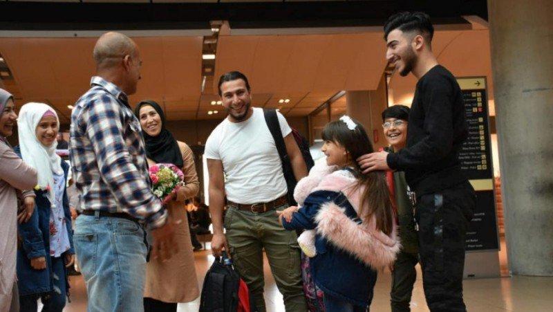 Ο Numeir (δεξιά) σμίγει επιτέλους και πάλι με την οικογένειά του στο αεροδρόμιο. Φωτογραφία: UNHCR/Chris Melzer)