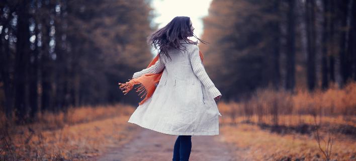Μια γυναίκα περπατάει χαρούμενη στο πάρκο, Φωτογραφία: Shutterstock