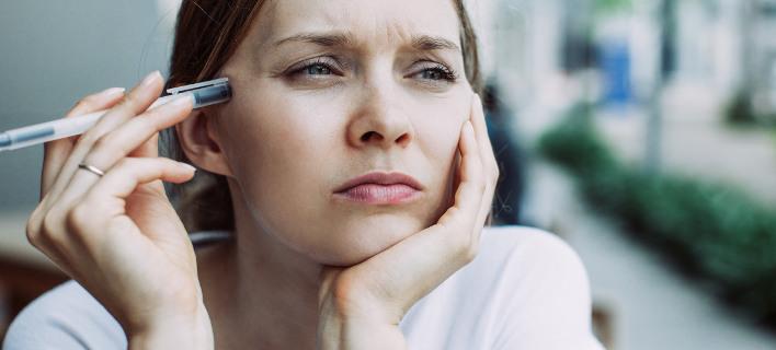 Γυναίκα κρατάει στυλό/Φωτογραφία Shutterstock