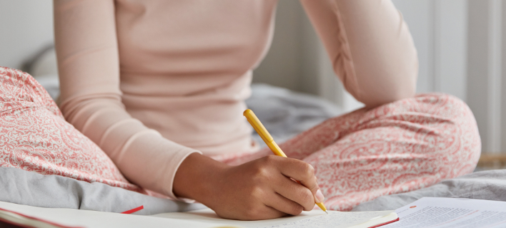Μια γυναίκα φοράει πιτζάμες στο κρεβάτι, Φωτογραφία: Shutterstock/By WAYHOME studio
