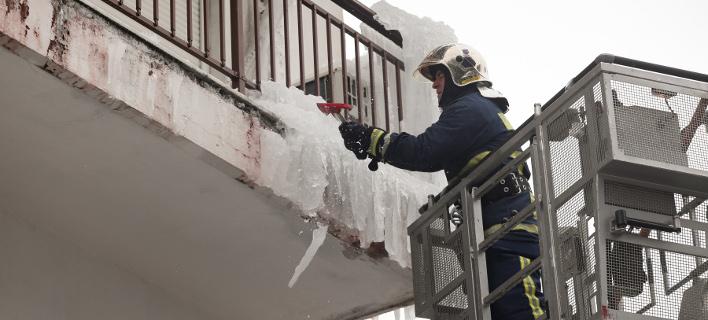 Πυροσβέστης σπάει το παγωμένο «γλυπτό» / Φωτογραφία: InTime News