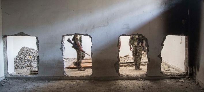 Άνδρες των SDF στο στάδιο όπου οι τζιχαντιστές του ISIS πρόβαλαν την τελευταία αντίσταση στη Ράκα (Φωτογραφία: ΑΡ)