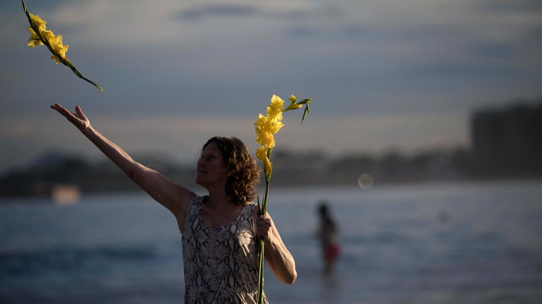Ρίο ντε Τζανέιρο: Μια γυναίκα προσφέρει λουλούδια στην θεά της θάλασσας, για το νέο έτος-Φωτογραφία: AP Photo/Leo Correa