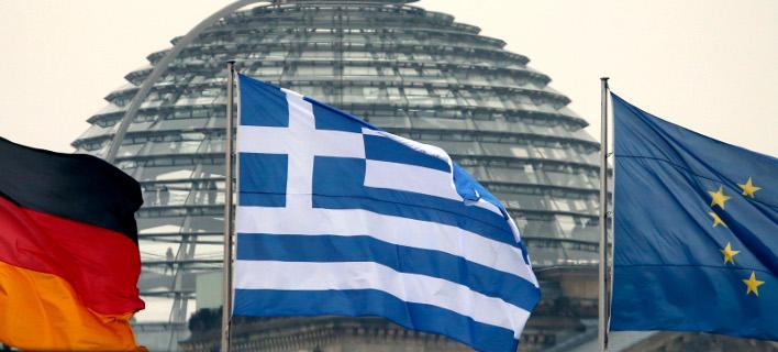 H γερμανική και ελληνική σημαία, καθώς και η σημαία της ΕΕ-Φωτογραφία: AP/Michael Sohn
