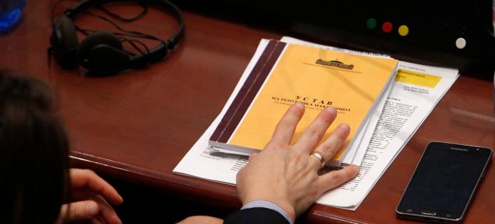 Βουλευτής της ΠΓΔΜ κρατά στο χέρι αντίτυπο του Συτνάγματος της χώρας στη διάρκεια συνεδρίας της Βουλής στα Σκόιπα (Φωτογραφία: ΑΡ/Boris Grdanoski)