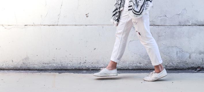 Μια γυναίκα φοράει λευκά πάνινα παπούτσια, Φωτογραφία: Shutterstock/Kugirlart