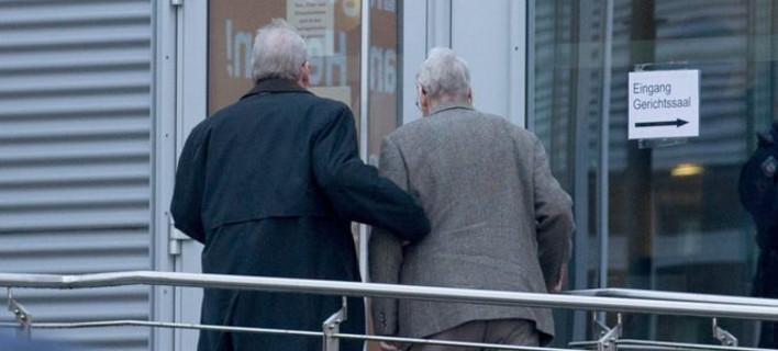 (ο Reinhold Hanning, 94, προσέρχεται υποβασταζόμενος στην δικαστική αίθουσα στο Detmold. φωτό: EPA)