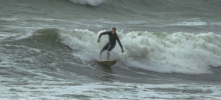Σέρφερ δαμάζει τα κύματα στην Εύβοια (Φωτογραφία: IntimeNews)