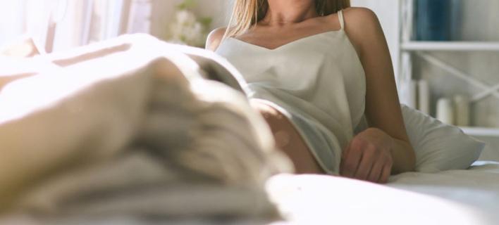 Μια γυναίκα ποζάρει στο κρεβάτι/ Φωτογραφία: Shutterstock