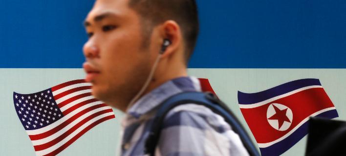Άντρας περνάει μπρόστα από τις σημαίες των ΗΠΑ και της Β. Κορέας. AP Photo/Andy Wong