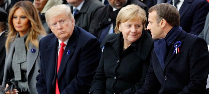 O Ντόναλντ Τραμπ εμφανίστηκε δυσαρεστημένος με τη «σφήνα» Μέρκελ ανάμεσα σε εκείνον και τον Εμανουέλ Μακρόν (Φωτογραφία: ΑΡ/Francois Mori, Pool)