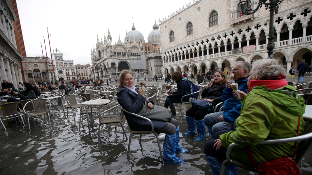 Τουρίστες αψηφούν τις πλημμύρες στη Βενετία και απολαμβάνουν το παγωτό τους στην πλατεία Αγίου Μάρκου -Φωτογραφία: AP Photo/Luca Bruno