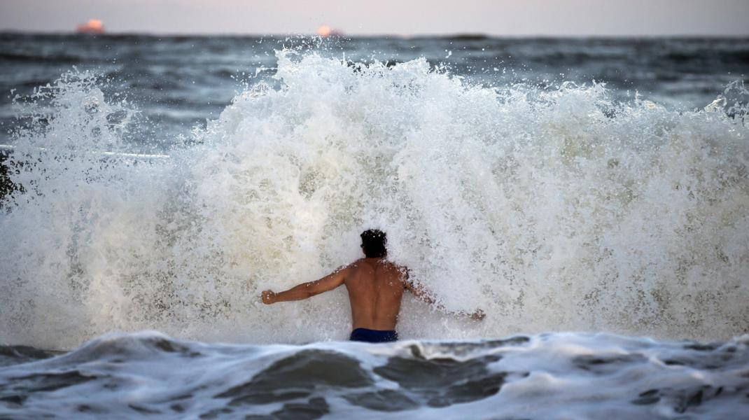 Ατρόμητος σέρφερ χαίρεται με τα κύματα που προκαλεί ο τυφώνας Φλόρενς που πλησιάζει τις ΗΠΑ -Φωτογραφία: AP Photo/Stephen B. Morton