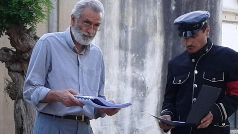 Αντρας με γαλάζιο πουκάμισο και ενας αστυνομικός