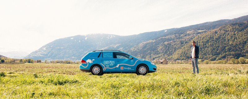 Ο Βίμπε Βάκερ, σε μια στάση, σε έναν καταπράσινο αγρό, μαζί με το μπλε, ηλεκτρικό αυτοκίνητό του, με το οποίο διήνυσε συνολικά 95.000 χιλιόμετρα.