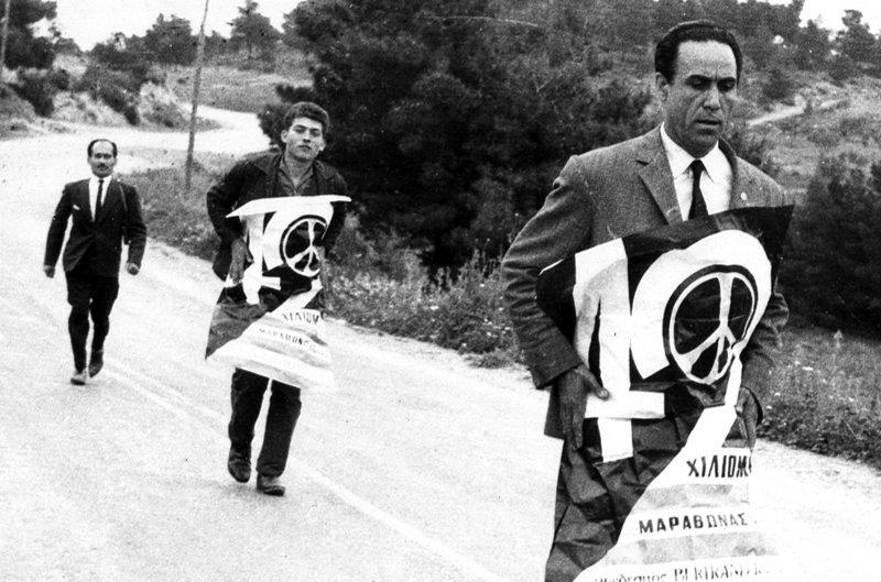 Ο Γρηγόρης Λαμπράκης συνεχίζει την Πορεία, τυλιγμένος με την αφίσα της Ειρήνης. Τον ακολουθούν οι Ανδρέας Μαμωνάς και Μπάμπης Παπαδόπουλος