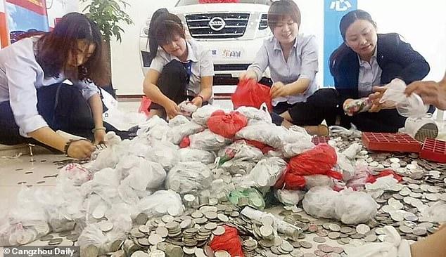 Υπάλληλοι μετρούν με τα χέρια, τα χιλιάδες νομίσματα / Φωτογραφία: Cangzhou Daily