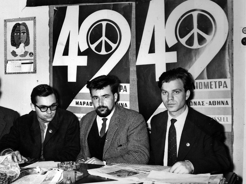 ΣΤΑ ΓΡΑΦΕΙΑ ΤΟΥ ΣΥΝΔΕΣΜΟΥ ΡΑΣΕΛ, στην οδο Ασκληπιού 3. Από αριστερά : Ο Νίκος Κιάος (Αντιπρόεδρος του Συνδέσμου), ο Πατ Ποτλ (Γραμματέας του Μπέρτραντ Ράσελ) και ο Μιχάλης Περιστεράκης (Πρόεδρος του Συνδέσμου). Έχουν πίσω τους τις αφίσες της Πορείας που αναγράφουν τον αριθμό των 42 χιλιομέτρων, όση είναι δηλαδή η απόσταση Μαραθώνα-Αθήνα .