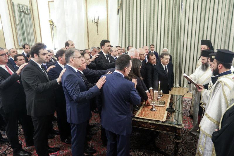Το χέρι στο Ευαγγέλιο από τους υπουργούς που βρίσκονται στην μπροστινή σειρά κατά τη διάρκεια της ορκωμοσίας