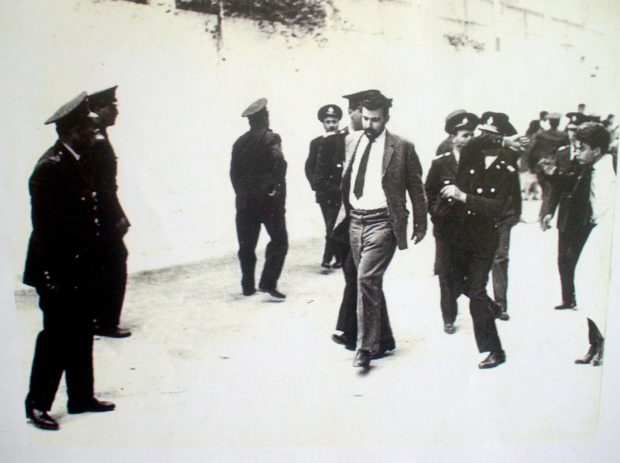 Ο Μιχ. Περιστεράκης συλλαμβάνεται από αστυνομικούς, ενώ ένας αξιωματικός σηκώνει το χέρι για να χτυπήσει τον Ποτλ.